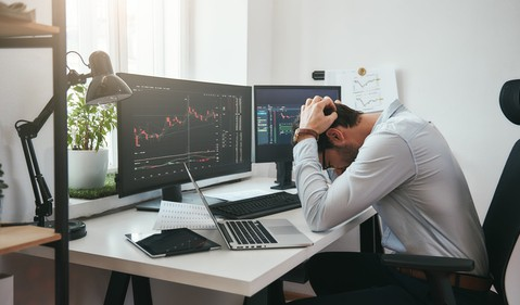 daytrader in distress in front of screens