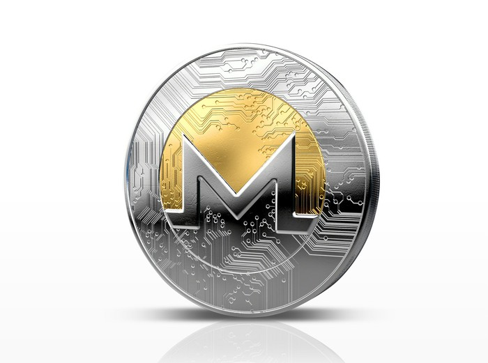 A silver and gold Monero XMR coin stood on its side.