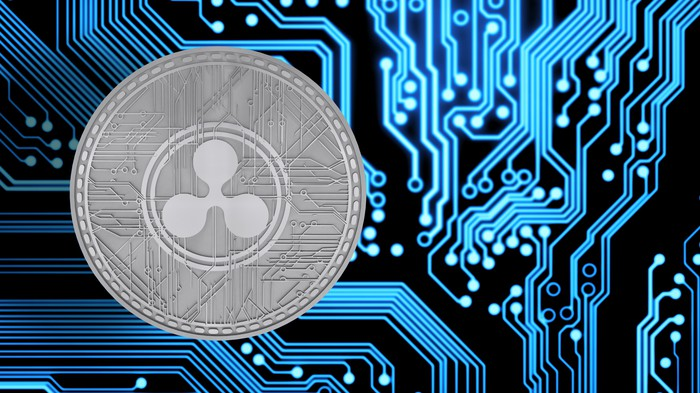 An up-close view of a physical silver XRP coin next to circuitry.
