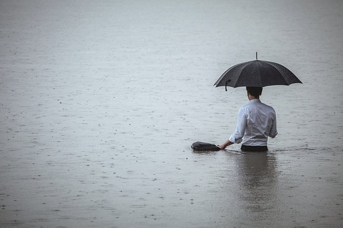 Man wading into water while holding an umbrella in the rain.