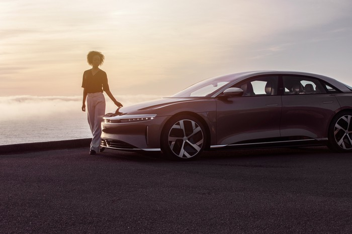 A person touches the hood of the Lucid Air luxury sedan in front of a background of crashing waves.