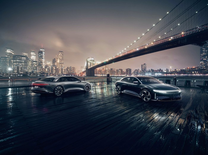 Two Lucid Air luxury sedans under a city bridge at night.