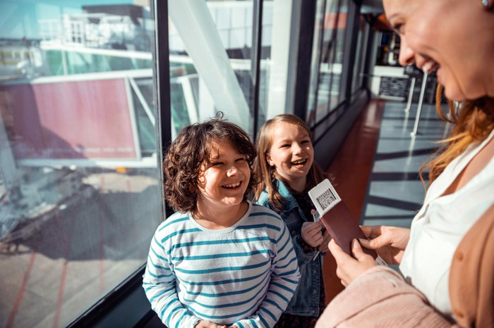 A person holding two boarding passes is seen smiling with two children in an airport.