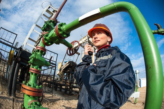 An oil and gas engineer speaking on a two-way radio while standing under pipeline.