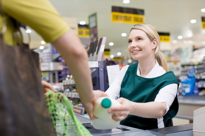Cashier checking customer out in a supermarket.
