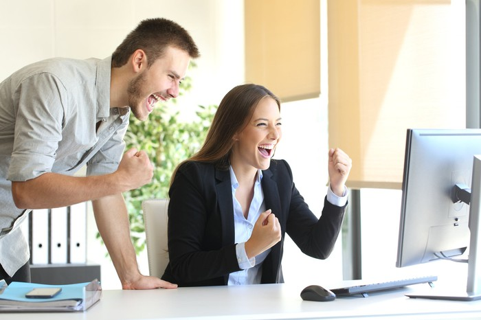 Two happy people cheer as they look at a computer monitor.
