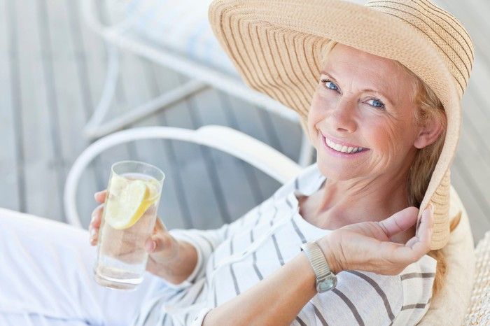 A woman wearing a large sun hat and drinking lemonade outside.