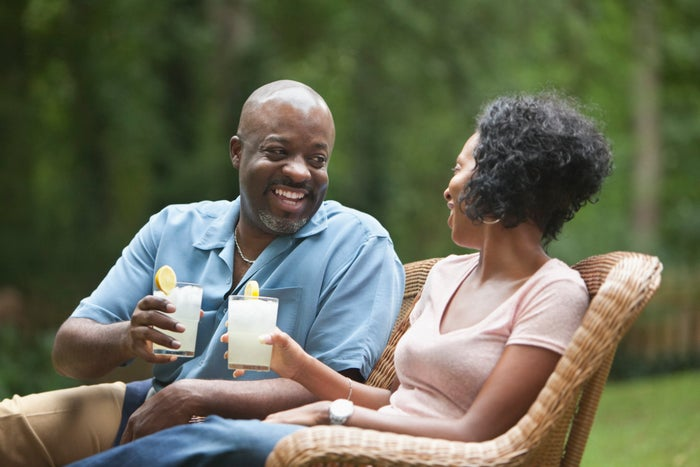 Two people sitting together and enjoying a drink of lemonade outside.