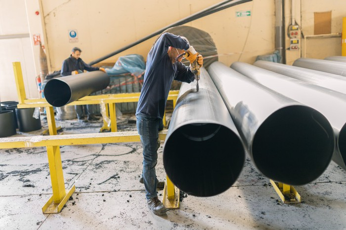 Men work on a big section of pipeline in a factory.