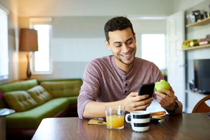 A person sitting at a table eating an apple while looking at his smartphone.