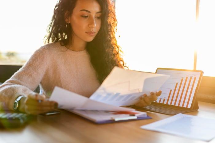 Young woman sitting at a desk looking at charts