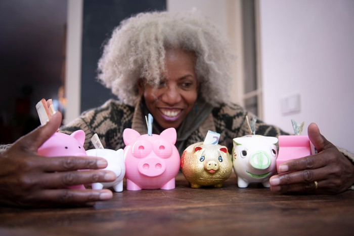 Person with armful of piggy banks.