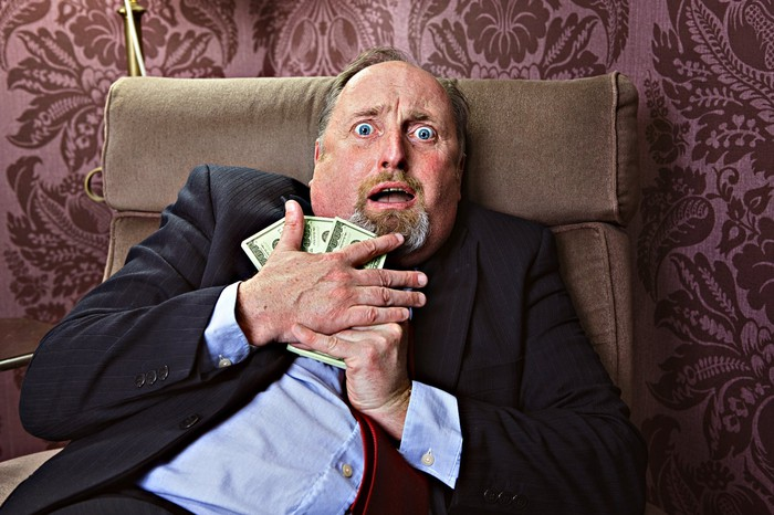 Scared person sitting in arm chair holding onto money.