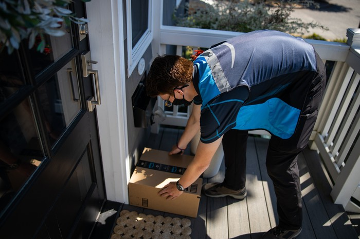 An Amazon driver placing a box by a door.