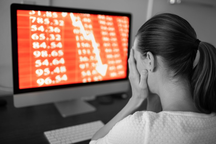 A person holding their face with a computer showing stock losses in the background.