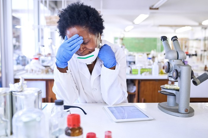 A scientist sitting at a laboratory bench expresses frustration as she consults a tablet computer sitting next to her microscope.