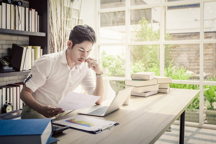 An investor studies notes on paper while in front of a computer.