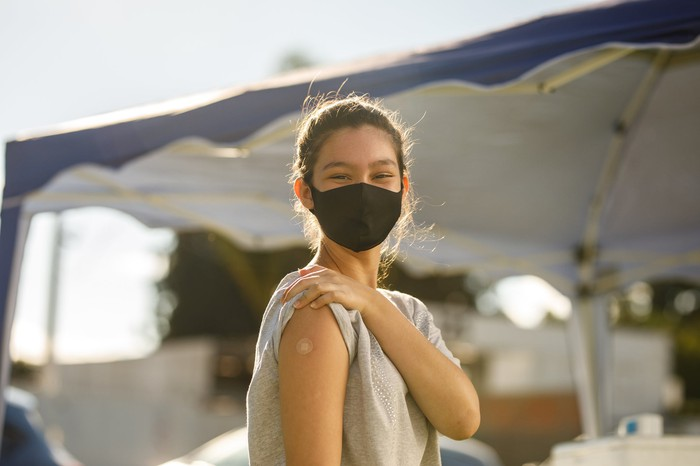 A teenage girl displays here vaccine sticker at a health center while wearing a mask.