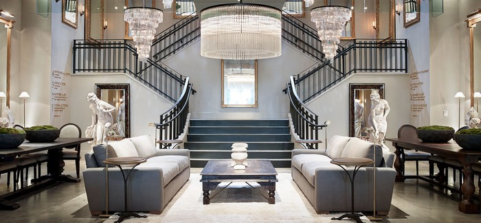 An upscale RH gallery store, with a grand staircase and sitting room furniture.