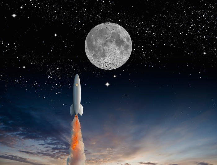 Rocket ship in space with background of moon and stars.