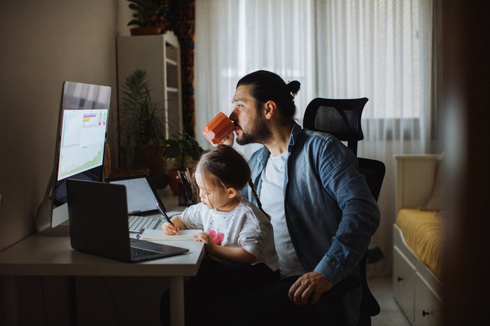 A parent sits with a child, sipping a hot drink and looking at stock data on a computer screen.
