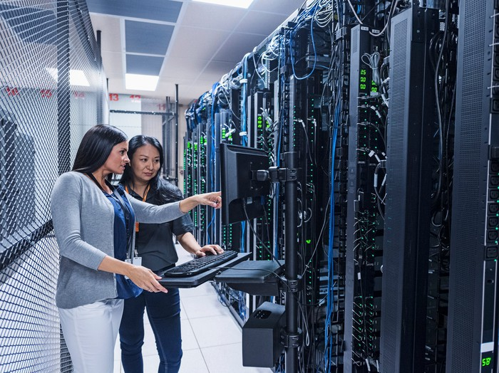 Two employees analyze an IT system while inside a server farm.