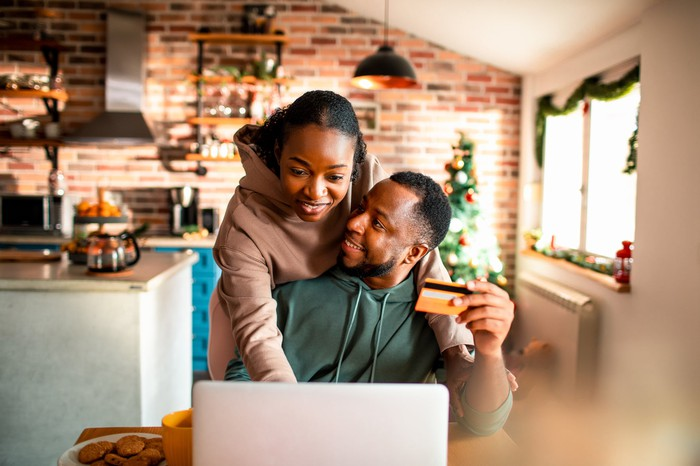 A couple in front of a computer in a home, with one person holding a credit card.