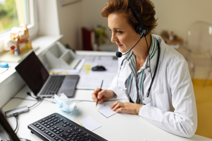 Doctor taking notes during online consultation.