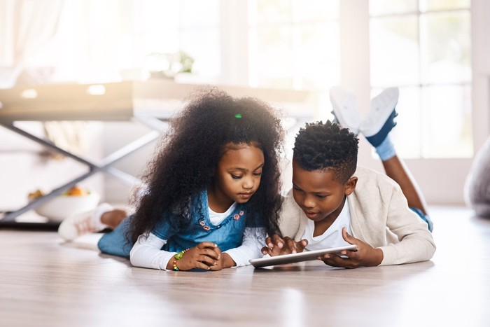 Two kids lay on the floor looking at a tablet.