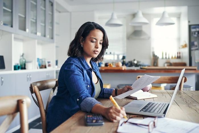 Une femme fait des calculs en regardant des papiers et son ordinateur portable.