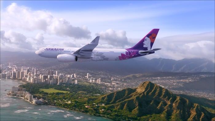 A Hawaiian plane flies over Honolulu.