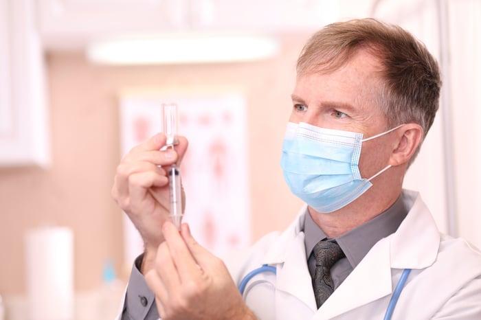 Doctor preparing syringe for coronavirus vaccine.