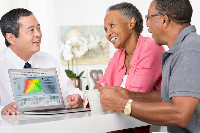 A person showing a laptop with a chart on it to two older people.