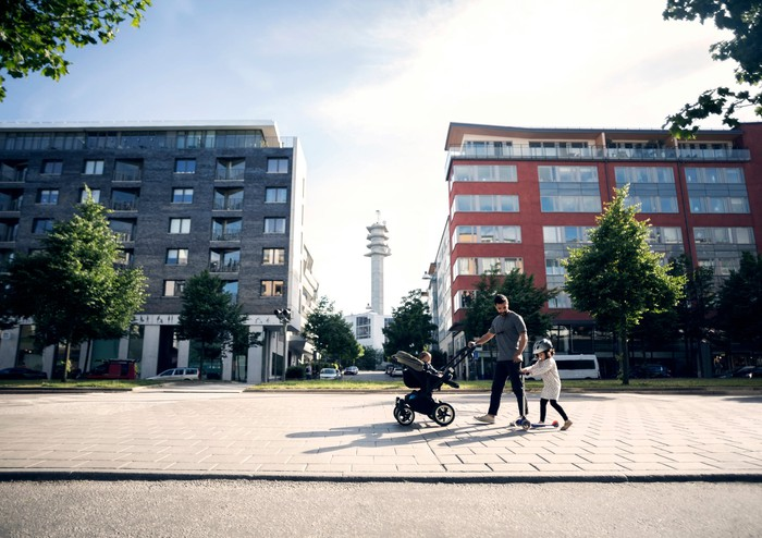 An adult walks with two children in front of apartment buildings.