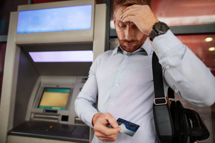Man near ATM machine looking down at debit card with concerning expression.