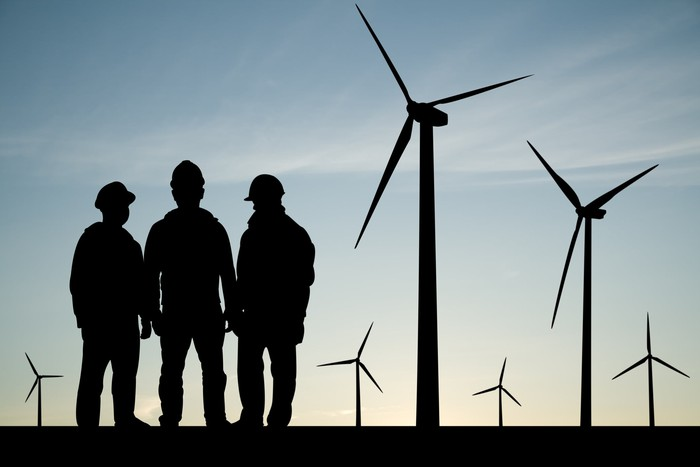 Three workers are shown in silhouette near six wind turbines.