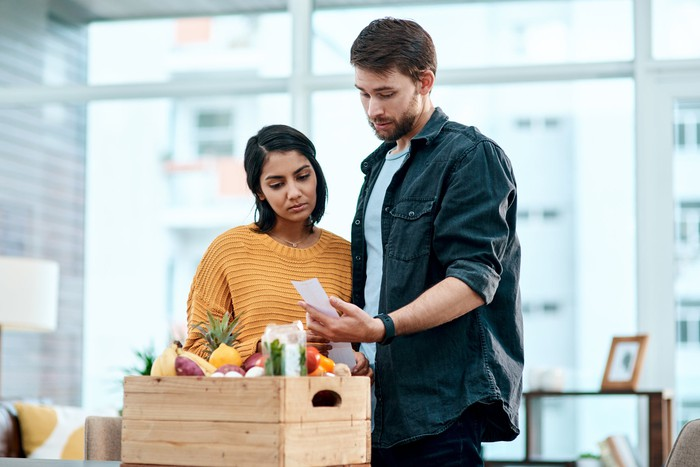 Two people looking at a box of food and the receipt for it.
