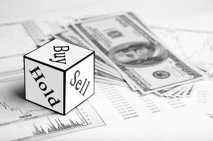 Dice with three visible sides that say buy, hold, and sell sitting on a stock chart next to a pile of one hundred dollar bills.