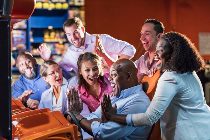 A group of people cheering on and high-fiving a man playing a sti-down arcade racing game.
