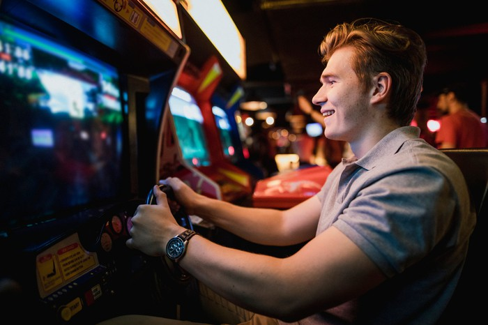 A young man playing an arcade game.