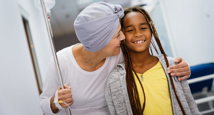 Cancer patient with IV smiling with child.