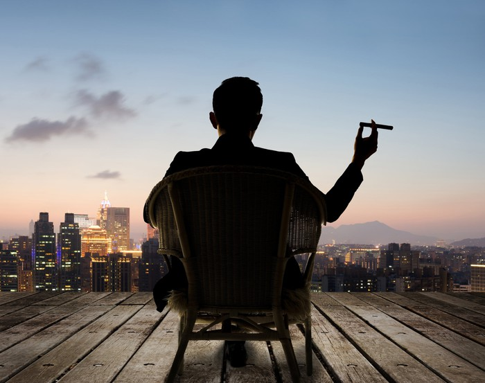 Person sitting in chair on deck overlooking city, holding cigar