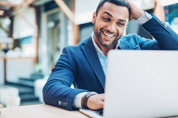 Smiling person in suit looking at laptop.