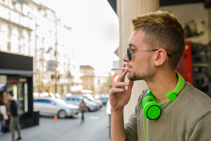 Person wearing green headphones and sunglasses stands outside, smoking.