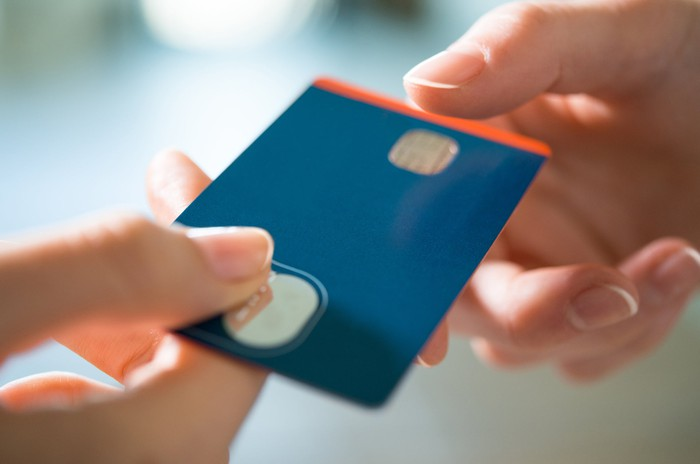Credit card being passed off between two hands.