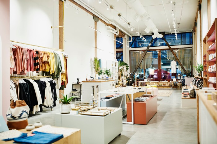 A brightly lit boutique store with a shelf of clothing and other luxury items on display.