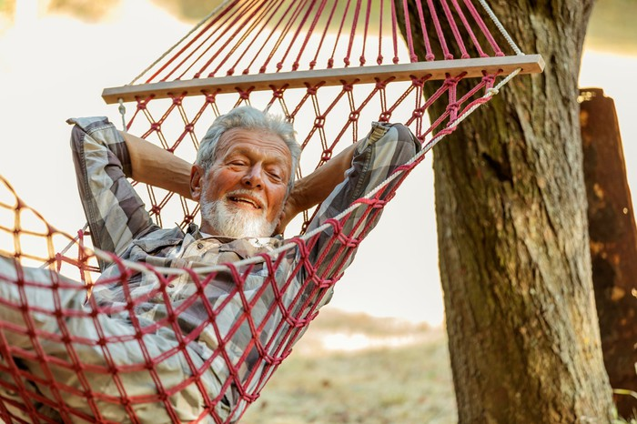 Smiling gray-haired person in hammock