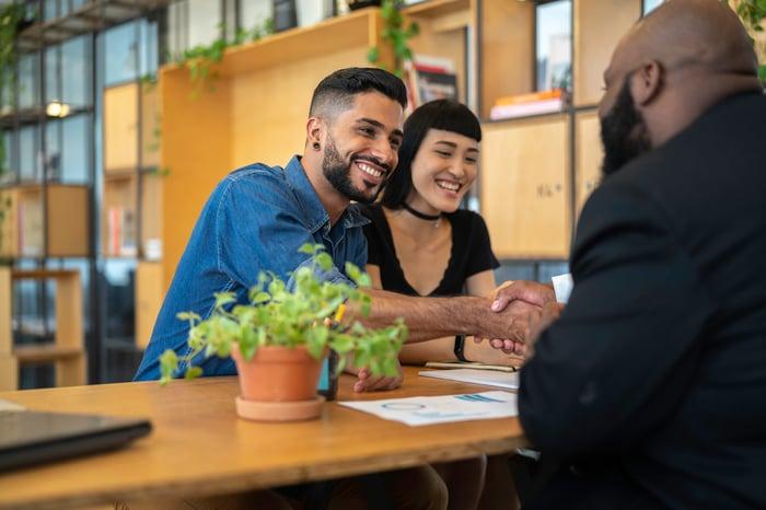 Un couple souriant se serrant la main sur un bureau avec un prêteur.