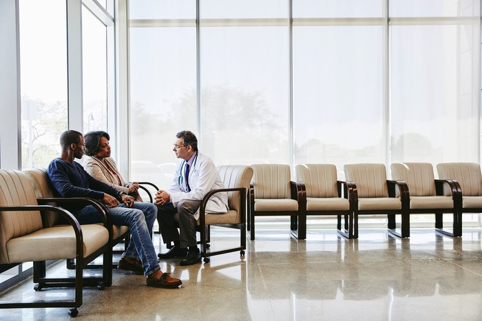 Doctor sitting with two people.