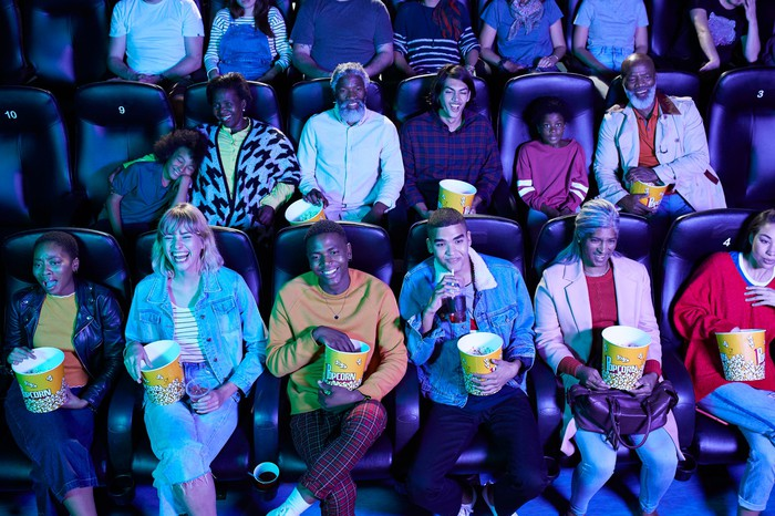 Several happy people watching a movie and eating popcorn in a theater.